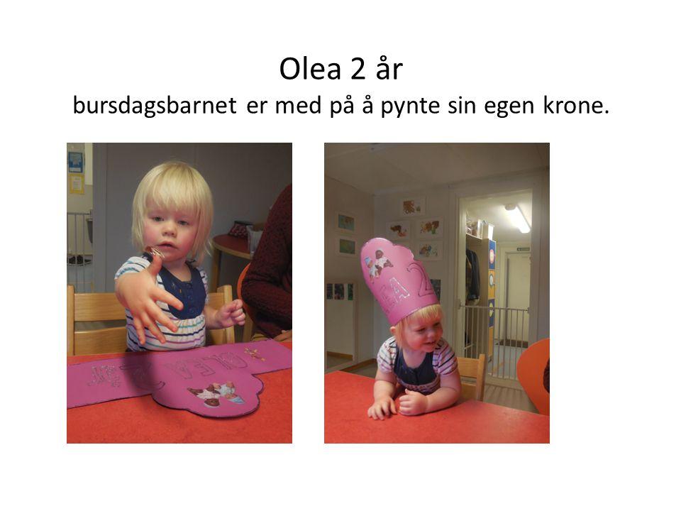 Olea 2 år bursdagsbarnet er med på å pynte sin egen krone.