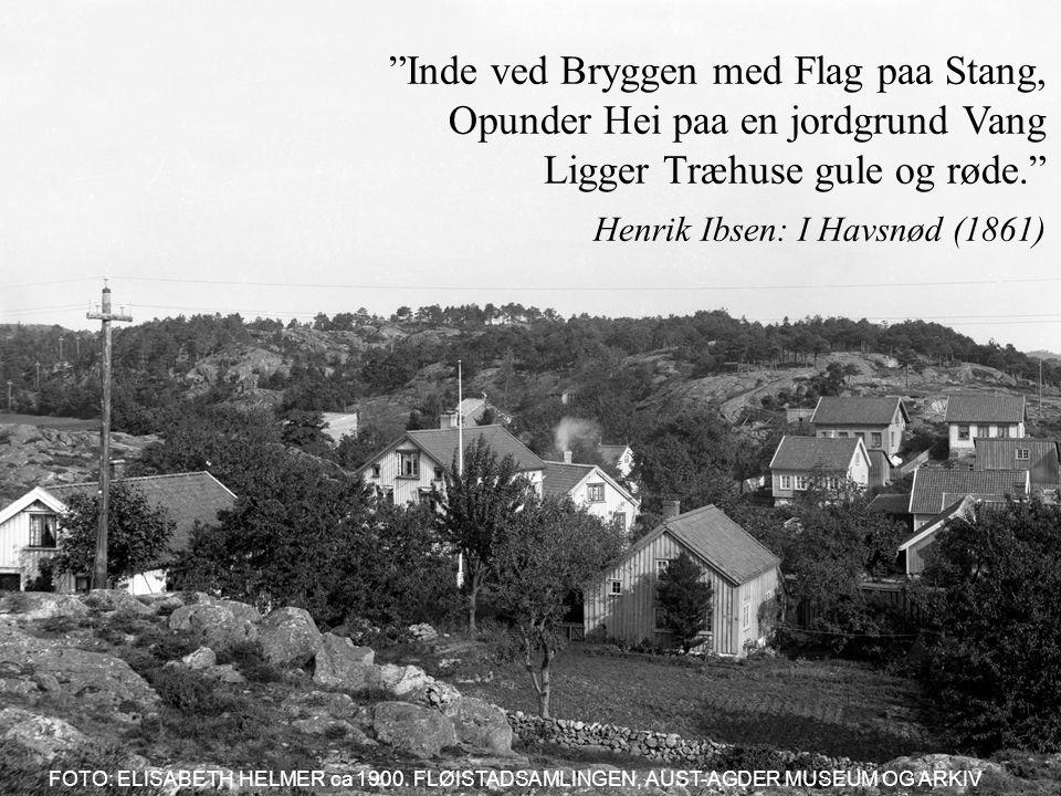 Inde ved Bryggen med Flag paa Stang, Opunder Hei paa en jordgrund Vang Ligger Træhuse gule og røde. Henrik Ibsen: I Havsnød (1861) FOTO: ELISABETH HELMER ca 1900.