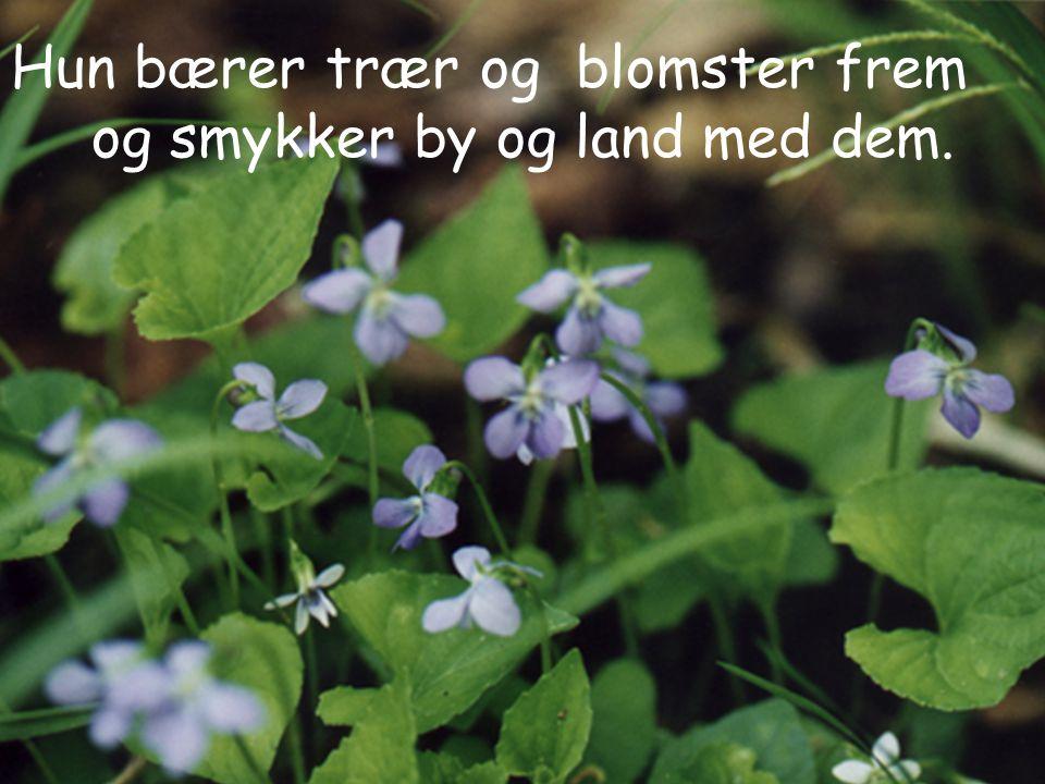 Hun bærer trær og blomster frem og smykker by og land med dem.