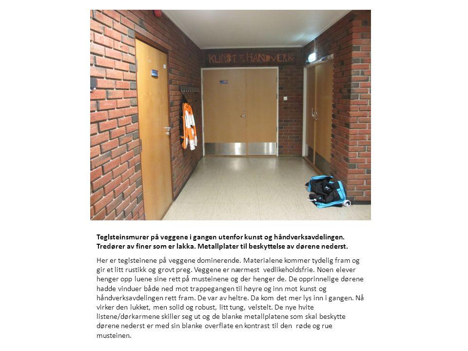 Teglsteinsmurer på veggene i gangen utenfor kunst og håndverksavdelingen. Tredører av finer som er lakka. Metallplater til beskyttelse av dørene neder