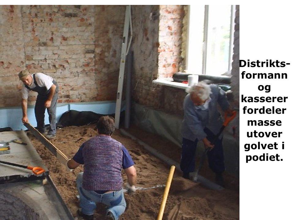 Distrikts- formann og kasserer fordeler masse utover golvet i podiet.