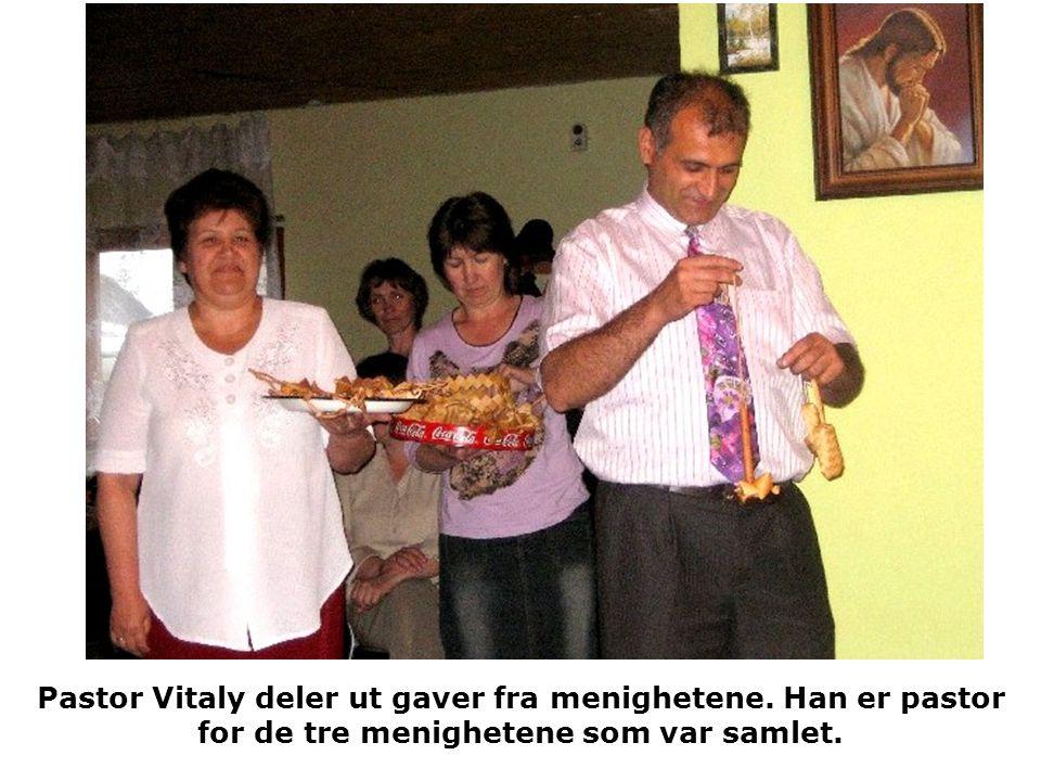 Pastor Vitaly deler ut gaver fra menighetene. Han er pastor for de tre menighetene som var samlet.